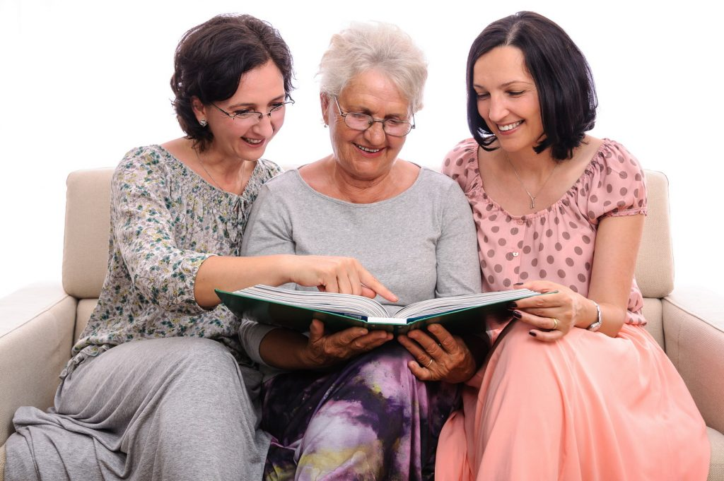 Mother and daughters enjoying photo album together.  Sharing Stories.